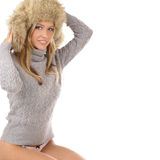 A young and sexy blond girl in a winter hat. A young and sexy blond girl in a sweater and a winter hat. The image is isolated on a white background Royalty Free Stock Image
