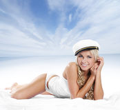 A young and sexy blond is laying in a sailor hat Royalty Free Stock Image