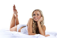 A young and sexy blond laying on a silk bed Royalty Free Stock Images