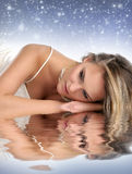 Young and sexy blond laying on a sky background Royalty Free Stock Images