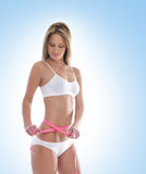 A young and sexy blond is measuring her waist Stock Images