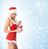 A young and sexy blond opening a Christmas present Stock Photos