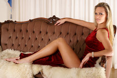 A young and sexy blond sitting on a brown sofa Royalty Free Stock Photography