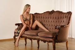 A young and sexy blond sitting on a brown sofa Royalty Free Stock Image