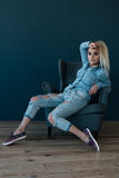 Young sexy blond woman in blue shirt and jeans sitting in a chair Royalty Free Stock Photo
