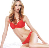 A young and sexy blond woman posing in red lingerie Royalty Free Stock Image