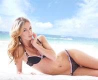 Young and sexy blond woman relaxing on the beach Stock Photos
