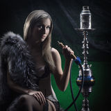 A young and sexy blond woman smoking a hookah Royalty Free Stock Image