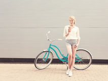 Young blond woman standing near a green vintage bicycle and holding a cup of coffeehave fun and good mood looking in camera a Royalty Free Stock Photo