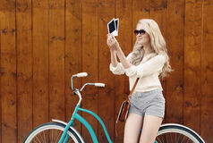 Young blond woman standing near a green vintage bicycle holding photos and smiling, warm, tonning Royalty Free Stock Images