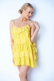 Sexy blond woman in yellow dress. Young and sexy blond woman in yellow dress smiling while  on white Stock Images