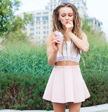 Young sexy blonde girl with dreads eating multicolored ice cream in waffle cones in summer evening,  joyful and cheerful.  Europea Royalty Free Stock Images