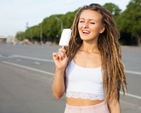 Young sexy blonde girl with dreads eating white ice cream in summer hot evening,  joyful and cheerful. Royalty Free Stock Photography