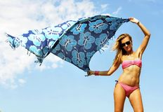 Young sexy blonde girl holding beach wrap to the air playing. With the cloth and the wind against a vivid blue sky in relax enjoying summer holidays feeling Royalty Free Stock Images