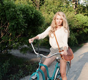 Young sexy blonde girl with long hair with brown vintage bag sits in a vintage bicycle Stock Photo