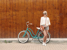 Young blonde girl with long hair in green sunglasses standing near vintage green bicycle have fun and good mood looking in ca Stock Images
