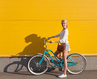 Young sexy blonde girl is standing near the vintage green bicycle with brown vintage bag Stock Photography