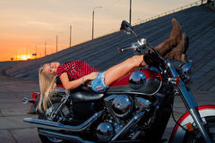 Young sexy blonde is lying on her motorcycle Royalty Free Stock Photo