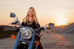 Young sexy blonde sitting on her motorcycle Stock Image