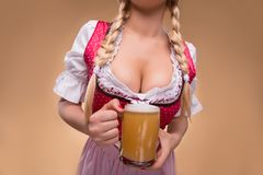 Young sexy blonde wearing dirndl. Half-length portrait of young sexy blonde with big breast wearing pink dirndl with white blouse holding the beer mug Isolated Stock Photo