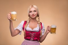 Young blonde wearing dirndl. Half-length portrait of young blonde wearing pink dirndl and white blouse holding in both hands beer mugs standing in indecision stock image