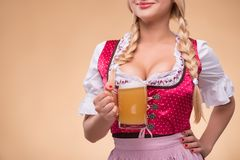 Young blonde wearing dirndl. Half-length portrait of young blonde wearing pink dirndl with white blouse showing us a big beer mug. Isolated on dark background stock photo
