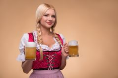 Young blonde wearing dirndl. Half-length portrait of young smiling blonde wearing pink dirndl and white blouse holding in both hands beer mugs looking at us royalty free stock images