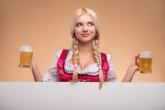 Young blonde wearing dirndl. Half-length portrait of young smiling blonde wearing pink dirndl and white blouse holding two beer mugs looking out of the big white royalty free stock images