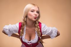 Young sexy blonde wearing dirndl. Half-length portrait of young sexy smiling blonde wearing pink dirndl with white blouse leaning to us showing her breast Stock Photos