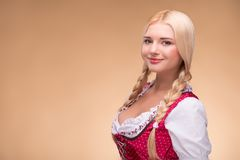 Young blonde wearing dirndl. Half-length portrait of young smiling blonde wearing pink dirndl with white blouse standing aside looking at us. Isolated on dark royalty free stock image