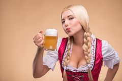 Young blonde wearing dirndl. Half-length portrait of young blonde standing aside wearing pink dirndl with white blouse adoring beer. Isolated on dark background royalty free stock images