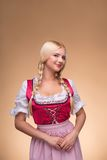 Young blonde wearing dirndl. Young shy smiling blonde wearing pink dirndl with white blouse looking at us mysteriously. Isolated on dark background stock image