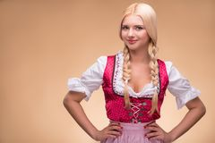 Young blonde wearing dirndl. Young smiling blonde wearing pink dirndl with white blouse looking at us putting her hands on her waist. Isolated on dark background stock image