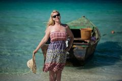Young blonde woman in beach dress near sea. Girl at the beach royalty free stock photo