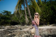 Young blonde woman in beach dress near sea. Girl at the beach stock photo
