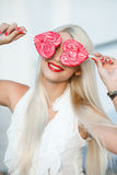 Young blonde woman with heart shaped lollipop Royalty Free Stock Images