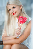Young blonde woman with heart shaped lollipop Royalty Free Stock Photography