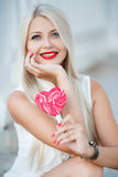 Young blonde woman with heart shaped lollipop Stock Photography