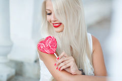 Young blonde woman with heart shaped lollipop Stock Photos
