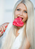 Young blonde woman with heart shaped lollipop Stock Photo