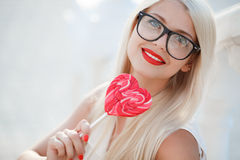 Young sexy blonde woman with heart shaped lollipop Royalty Free Stock Image