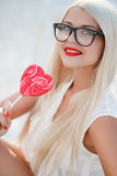 Young sexy blonde woman with heart shaped lollipop Royalty Free Stock Photos