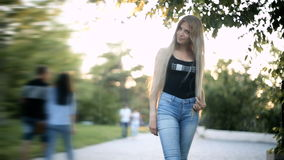 Young blonde woman long flowing hair is walking in the park backlight from the sun is shining stock footage