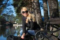 Young blonde woman in a park. Young attractive woman with long blonde hair in a park royalty free stock photography