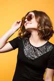 Young sexy blonde woman posing in the yellow wall, wearing black dress, mirrored sunglasses, Royalty Free Stock Images