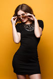 Young sexy blonde woman posing in the yellow wall, wearing black dress, mirrored sunglasses, Stock Image