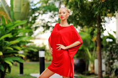 Young blonde woman in red dress posing outdoor Royalty Free Stock Photography