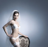 A sexy bride posing in white erotic lingerie on a chair Stock Image