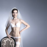 A sexy bride posing in white erotic lingerie on a chair Stock Photos