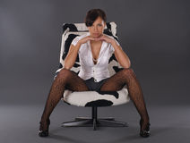 A young and sexy brunette businesswoman in a chair Royalty Free Stock Photo